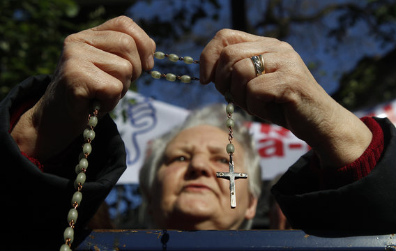 Catholic faithful prays during a protest against the construction of a modern office building, erected next to the Saint Joseph cathedral, in Bucharest
