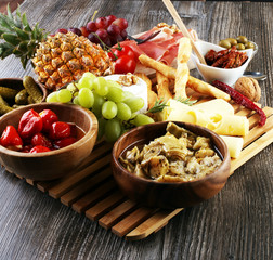 Italian antipasti wine snacks set. Cheese variety, Mediterranean olives, pickles, Prosciutto di Parma over black grunge background