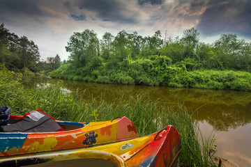 Kayaks sitting on a green grassy riverbank.