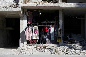 A vendor stands near secondhand clothes displayed for sale in Ain Tarma, in the eastern Damascus suburb of Ghouta