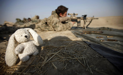 A German Bundeswehr army paratrooper sniper of the Task Force Kunduz opens fire next to a mascot during a drill in Kunduz
