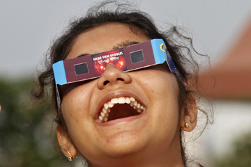 A girl reacts as she uses a pair of eclipse glasses to watch Venus passing the sun in Kolkata