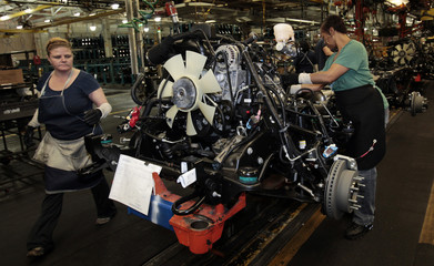 Two female General Motors auto assembly workers  assemble engines for the Chevrolet Silverado and GMC Sierra pickup trucks at the Flint Assembly in Flint, Michigan