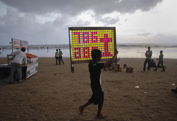 A boy carries a wooden frame with canisters filled with soap water on a beach in Mumbai