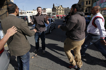 Supporters of Respect Party candidate George Galloway confront a man throwing eggs at his campaign office in Bradford