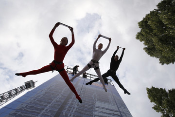 People perform on the side of a building during a Lenovo presentation of a laptop and tablet PCs during press day at the IFA consumer electronics fair in Berlin