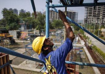 A student climbs a scaffolding at an outdoor classroom at the Larsen & Toubro construction skills training institute in Panvel