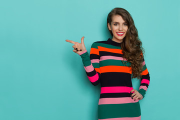 Smiling beautiful young woman in colorful vibrant striped dress is posing with hand on hip, pointing and looking at camera. Three quarter length studio shot on turquoise background. Wall mural