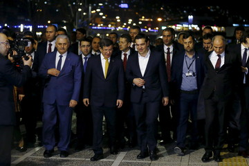 Turkish Prime Minister Ahmet Davutoglu (R) and his Greek counterpart Alexis Tsipras walk the city in the Aegean port city of Izmir
