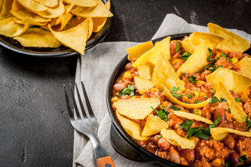 Traditional Mexican Chilean food, chili con carne, served in a portioned skillet pan with nachos tortilla. On black concrete table, close view copy space