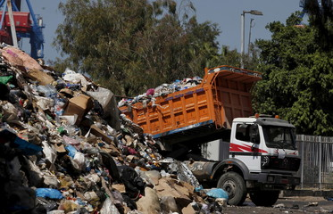 A truck unloads trash into a garbage filled-area on the edge of Beirut river, Lebanon