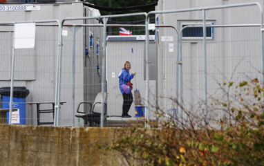 A woman mops outside temporary accommodation for workers of the London 2012 Olympic Park at Stratford in London