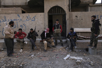Members of the Jund Allah Brigades, part of the Free Syrian Army, sit along a street as they hold their weapons in Deir al-Zor