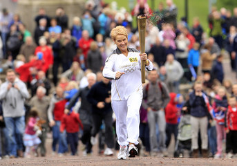 Geraldine McCann carries the Olympic torch towards Parliament Buildings in Belfast