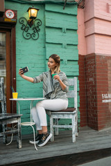 Young fashion woman drinks cappuccino outside a cafe ,smiling while taking selfies