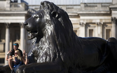 A couple pose for a photograph next to a statue of a lion on a sunny day in Trafalgar Square in London, Britain