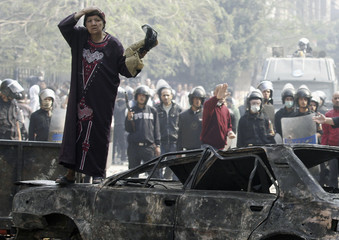 Protesters take cover behind a damaged car along a road which leads to the Interior Ministry, near Tahrir Square in Cairo