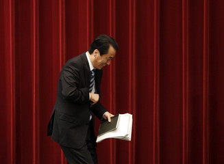 Japan's Prime Minister Naoto Kan smiles as he leaves a news conference at his official residence in Tokyo