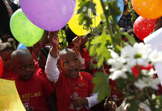 Children hold balloons and flowers as they gather to wish to former President Nelson Mandela happy birthday in Pretoria