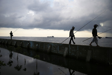 Men hold fishing rods as they walk on a sea wall at Muara Baru port in Jakarta