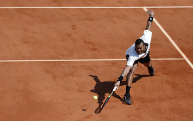 Jo-Wilfried Tsonga of France returns the ball to Stan Wawrinka of Switzerland during their men's semi-final match at the French Open tennis tournament at the Roland Garros stadium in Paris