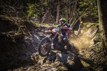 Motocross rider passes through the mud on the hardenduro race