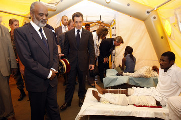 France's President Sarkozy and Haitian President Preval speak with earthquake survivors during a visit to a French field Hospital inside the Alexandre Dumas French school in Port-au-Prince