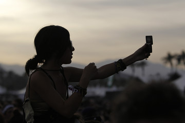 """A concert-goer takes a photo before the performance of """"The xx"""" at the Coachella Music Festival in Indio"""