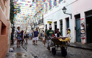 "A street fruit vendor wears a t-shirt that reads ""Brasil"" as he walks under decorations for the 2014 World Cup at Pelourinho neighborhood in Salvador"