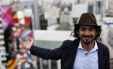 Brazilian graffiti artist Kobra gestures in front of his piece of art in tribute to Brazilian architect Niemeyer during an interview with Reuters at the financial center in Sao Paulo
