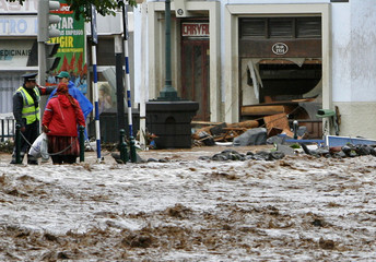 People talk with a police officer along a heavily flooded street in downtown Funchal