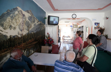 People watch the television broadcast of former Bosnian Serb army chief Ratko Mladic's court proceedings in a small restaurant in Potocari