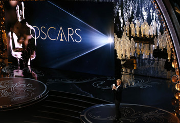 Ellen Degeneres takes a picture of the audience as she hosts the show at the 86th Academy Awards in Hollywood