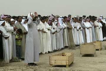 Residents pray over coffins bearing remains of bodies during a funeral in Falluja
