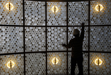 A construction worker touches up a wall made with plastic bottles inside the EcoArk building during a media preview in Taiwan