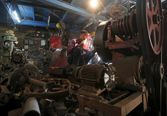 A worker welds an automobile gear casing at a workshop in an industrial area in Mumbai