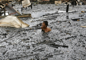 A man shouts in pain as he steps onto a sharp object while searching for salvageable items in water after a fire in a slum in Malabon City