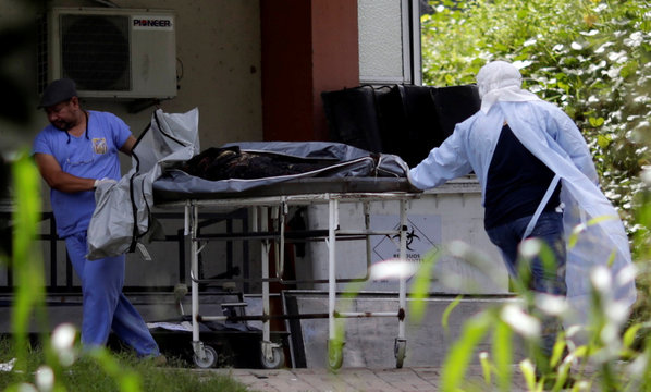 Staff work next to the body of an inmate, who died during a prison riot, at the Medical Legal Institute in Manaus