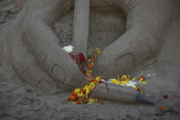 Flowers are seen scattered on a broken pencil sand sculpture made by an artist in tribute to the victims of a shooting by gunmen at the offices of French satirical weekly Charlie Hebdo, at a beach in Mumbai