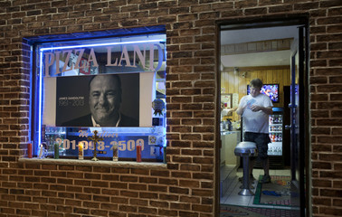 Delivery driver checks order before leaving Pizza Land restaurant, as a memorial to deceased actor Gandolfini is seen in its front window in North Arlington, New Jersey