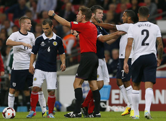Match referee Brych signals as England and Scotland players confront each other during their international friendly soccer match in London
