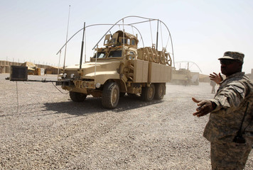 A U.S. military personnel directs a military vehicle as they prepare to hand over their base to Iraqi forces in Iraq's southern province of Basra