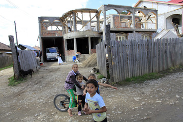 Roma children play in front of an unfinished house in Calvini village