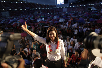 Yingluck Shinawatra, sister of ousted premier Thaksin Shinawatra, shows her trademark one finger sign as she takes a stage for the last big pre-election rally for her Puea Thai party at a stadium in Bangkok