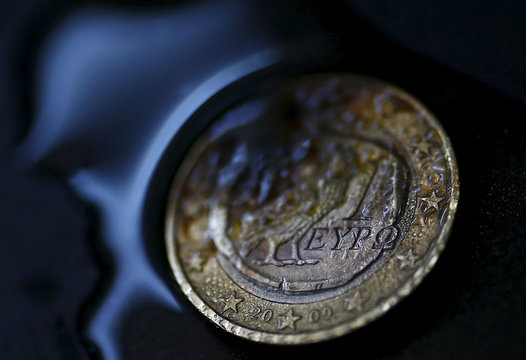 A one Euro coin with a Greek owl is seen burning in this picture illustration taken in Hanau