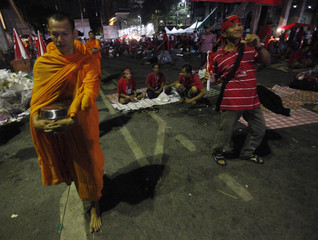"""An anti-government """"red shirt"""" protester dances as Buddhist monks walk past to receive food offerings in the main shopping district in Bangkok"""