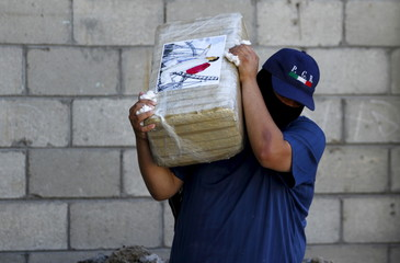 An agent of the office of the Attorney General of Mexico carries a package of seized marijuana at the site of a passageway Mexican authorities on Thursday attributed to the cartel of fugitive kingpin Guzman in Tijuana