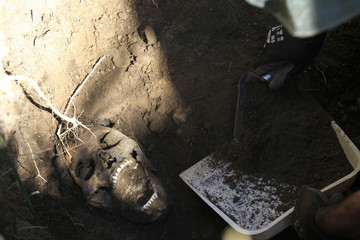A forensic technician removes sand near a human skull inside a cordoned-off area during an exhumation at a hidden mass grave discovered in Lourdes