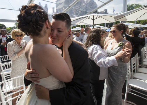 """Murphy and St. Germain dance after the ceremony for """"The Celebration of Love"""", a grand wedding where over 100 LGBT couples got married, at Casa Loma in Toronto"""