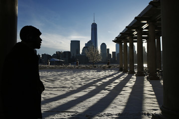 New York skyline and the One World Trade Center are seen in the distance as man makes his commute after a night of snow to  Exchange Place in New Jersey